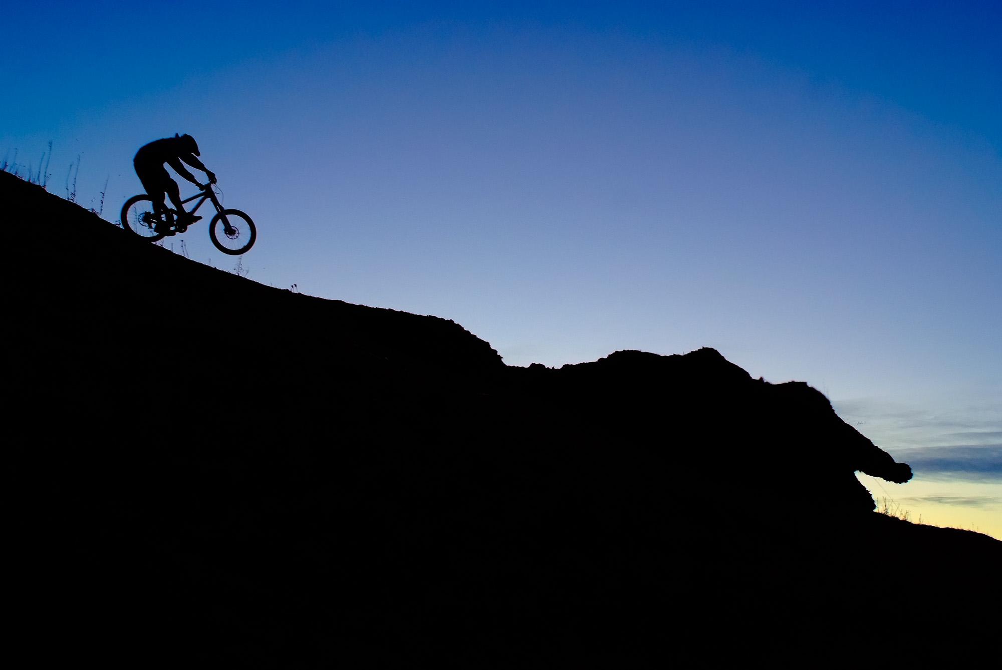 Riding ridgelines on the Banshee Legend. Sunset silhouette above Broxburn