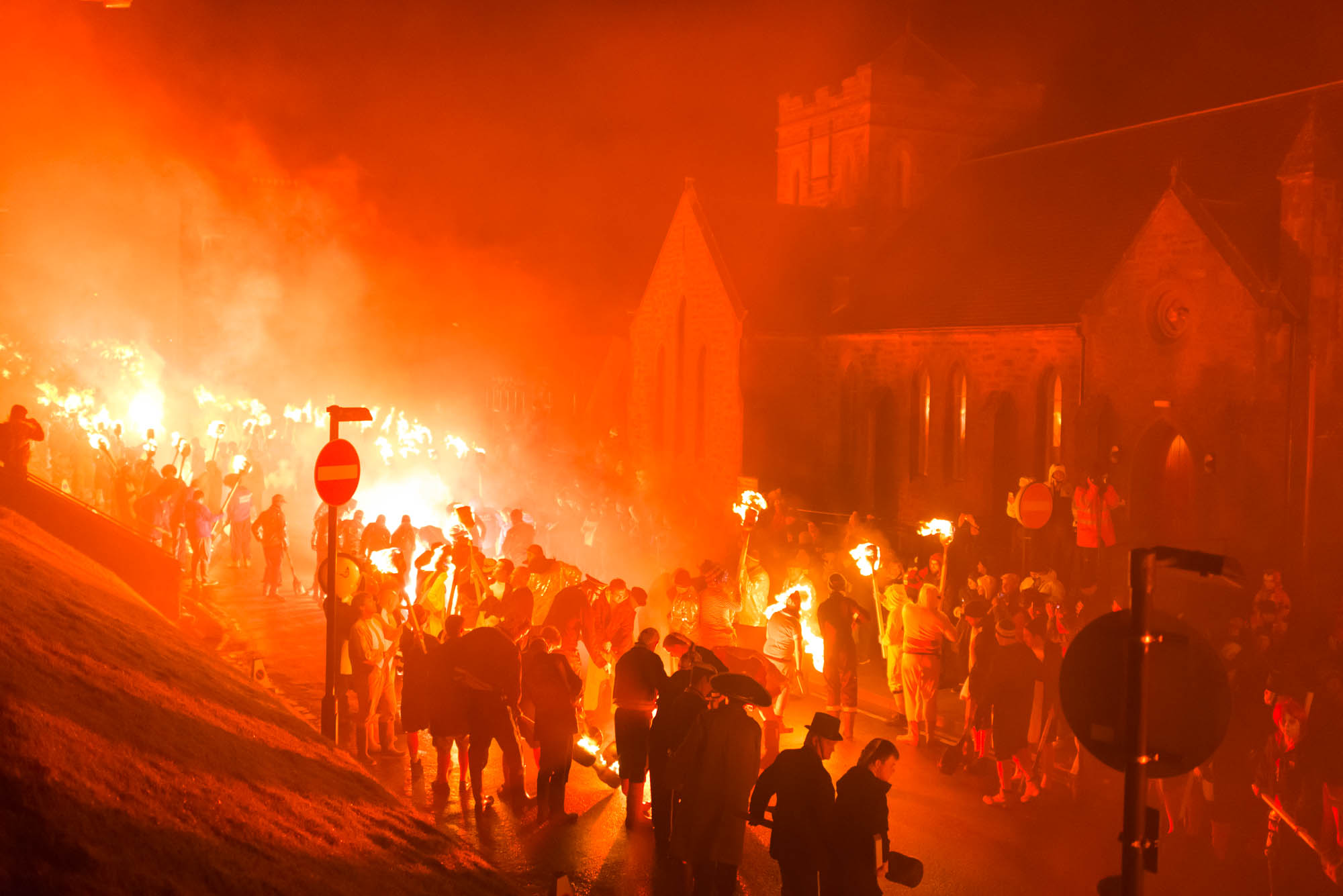 Up Helly Aa participants light their torches in preparation for the Torchlit Procession