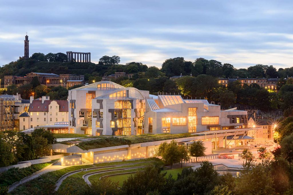 Architecture photography of The Scottish Parliament building, early evening with lights on.