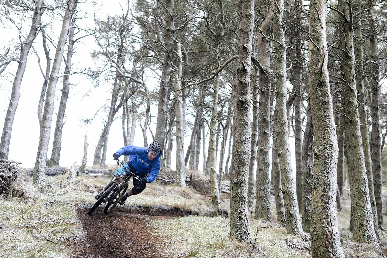 Mountain biker riding fast enduro trail through snowy forest in Scotland.