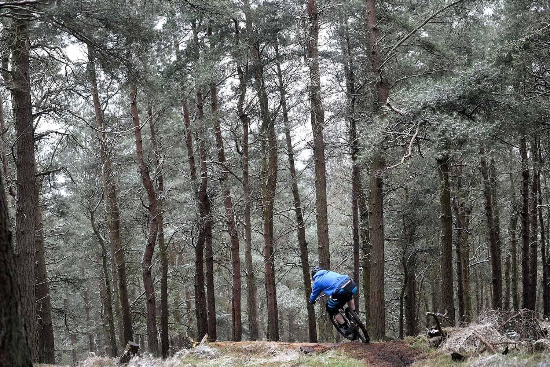 Mountain biker scrubbing into steep descent through wintery forest